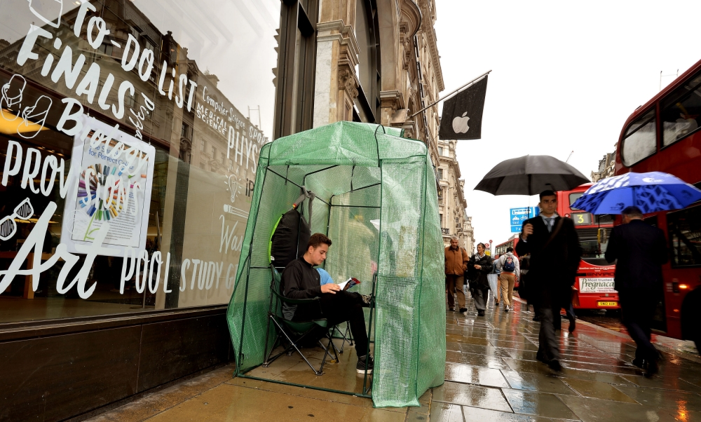 CAPTION CORRECTION AMENDING NAME OF SUBJECT FROM GAD HARARI to NOAH GREEN. CAPTION SHOULD READ  Noah Green aged 17, from London, sits in his plastic greenhouse which is the only shelter for himself as he waits to buy the new iPhone in Regent Street central London, which goes on sale in the UK this coming Friday. PRESS ASSOCIATION Photo. Picture date: Tuesday September 17, 2013. Photo credit should read: John Stillwell/PA Wire