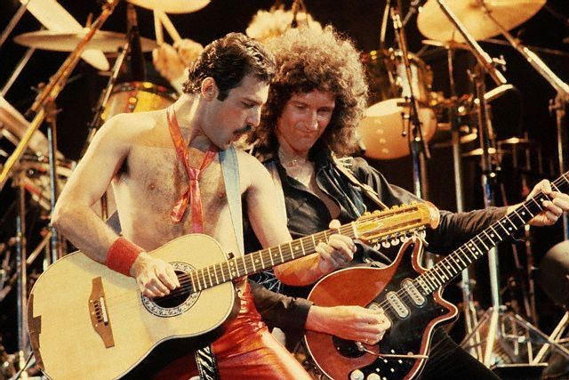 Freddie Mercury and Brian May play guitars in front of Roger Taylor's drums during a Queen concert. --- Image by   Neal Preston/CORBIS ca. 1980s