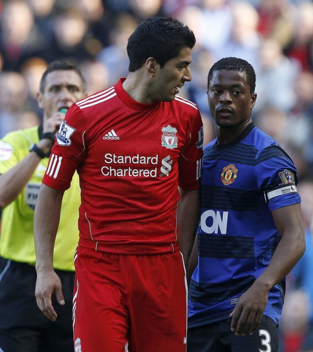 Liverpool's Luis Suarez (L) looks at Manchester United's Patrice Evra (R) during their English Premier League soccer match at Anfield in Liverpool, northern England in this October 15, 2011 file photo. Suarez has been banned for eight matches and fined 40,000 pounds ($62,800) for racially abusing Evra during the Premier League match at Anfield, the FA said on December 20, 2011. Photo taken on October 15, 2011. REUTERS