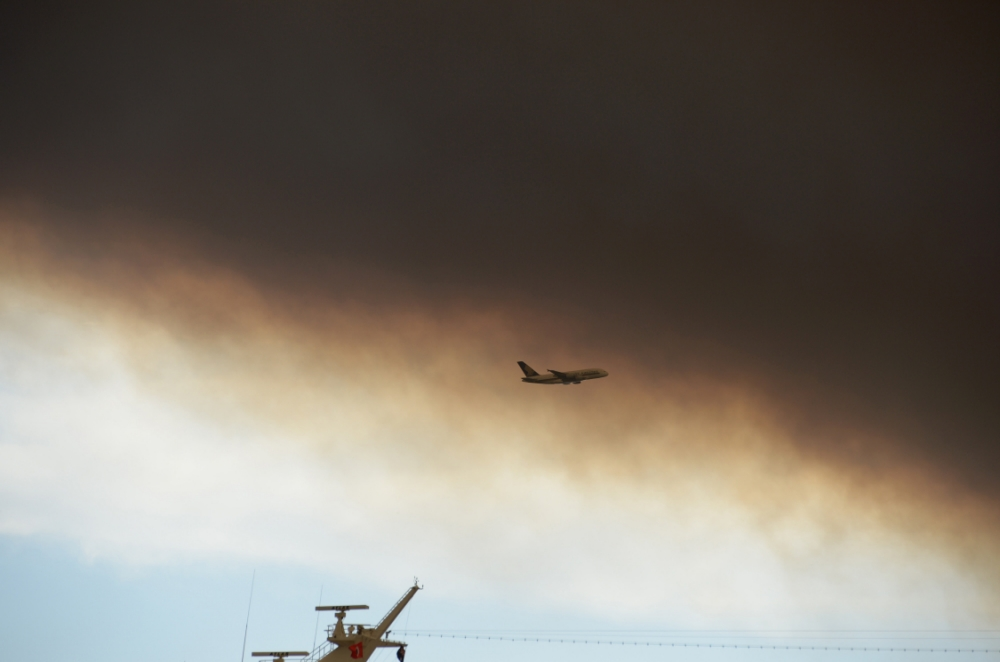 A plane (C) takes off as smoke and ash from wildfires burning across the state of New South Wales blankets a cruise ship (below) in Sydney Harbour on October 17, 2013. Seven major blazes were burning across the state, fanned by high, erratic winds in unseasonably warm 34 Celsius (93 Fahrenheit) weather, with infernos at Springwood and Lithgow in the Blue Mountains west of Sydney sending thick plumes of smoke and ash across the city. AFP PHOTO / Greg WOODGREG WOOD/AFP/Getty Images