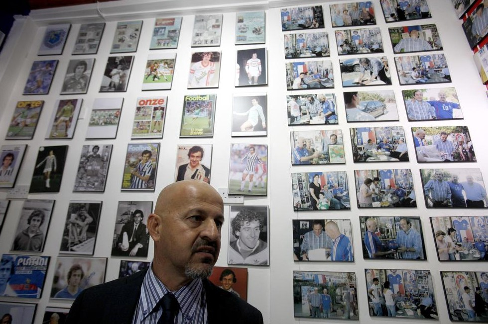 Philippos Stavrou Platini, owner of a museum dedicated to Michel Platini, poses next from photos of the France legend (Picture: AP)