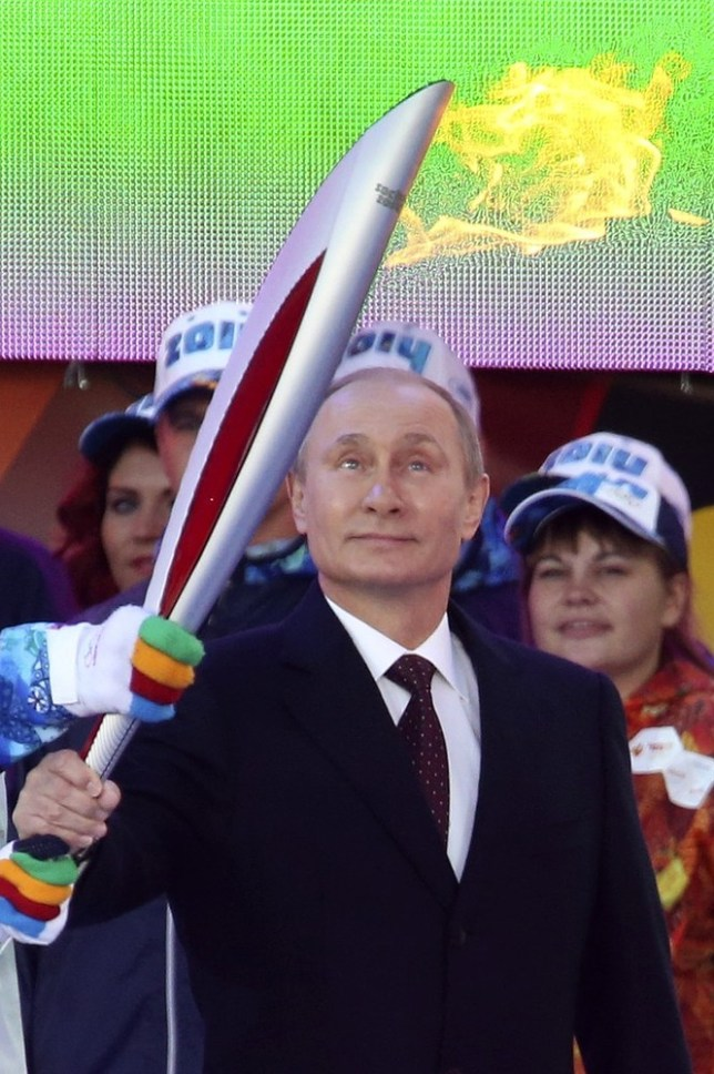 Russian President Vladimir Putin holds a lit Olympic torch during a ceremony to mark the start of the Sochi 2014 Winter Olympic torch relay in Moscow October 6, 2013. The flame that will burn at the Sochi 2014 Winter Games arrived in Moscow on Sunday, starting an epic torch relay around the huge country and bringing Vladimir Putin's campaign to stage Russia's first post-Soviet Olympics a step closer to completion. REUTERS