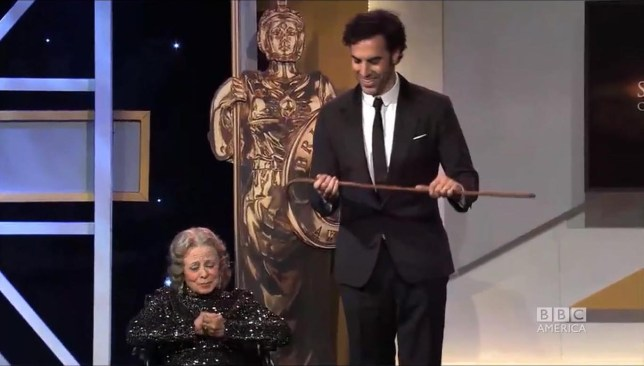 Grace Collington presents Sacha Baron Cohen with one of Charlie Chaplin's famous canes (Picture: BBC America)