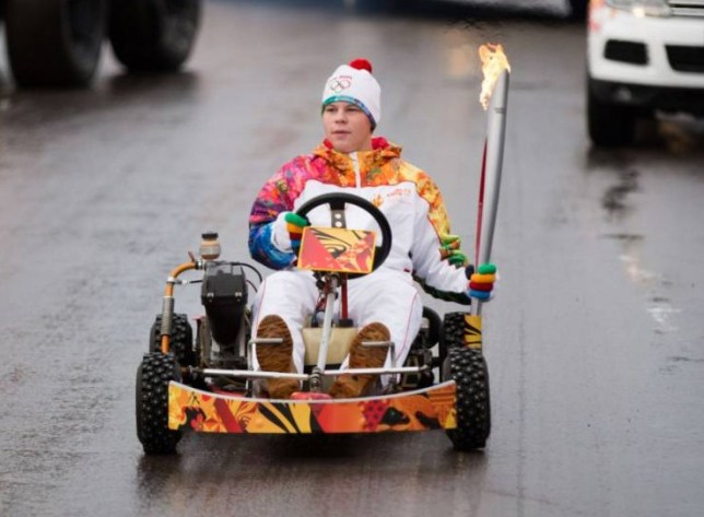"""A handout picture taken on November 1, 2013, and released by the Sochi 2014 Winter Olympics Organizing Committee shows a torchbearer holding a torch with the Olympic flame as he rides in a kart during the Sochi 2014 Winter Olympic torch relay  in the Russian city of Severodvinsk, some 1046 km (650 miles) north of Moscow. Russian torchbearers has started in October the history's longest Olympic torch relay ahead of February's Winter Games in Sochi, which will take the flame across the country through all 83 of its regions, including extreme locales such as Chukotka, the remote region in Russia's Far East, the turbulent North Caucasus, and even Russia's European exclave Kaliningrad. AFP PHOTO / SOCHI 2014 ORGANIZING COMMITTEE RESTRICTED TO EDITORIAL USE - MANDATORY CREDIT """"AFP PHOTO / SOCHI 2014 ORGANIZING COMMITTEE"""" - NO MARKETING NO ADVERTISING CAMPAIGNS - DISTRIBUTED AS A SERVICE TO CLIENTS-HO/AFP/Getty Images"""