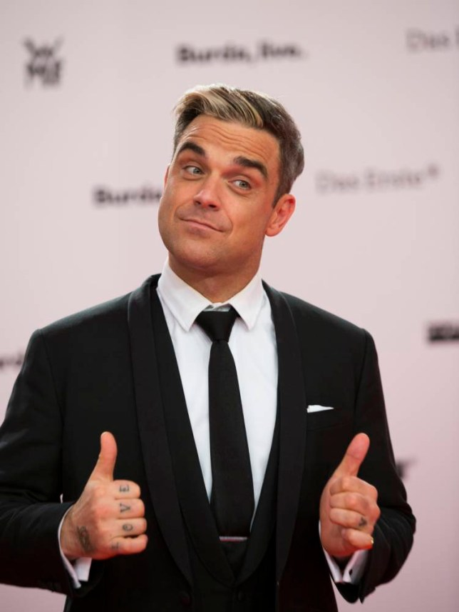 Robbie Williams arrives for the Bambi 2013 media awards in Berlin, Germany, Thursday, Nov. 14, 2013. (AP Photo/Gero Breloer)