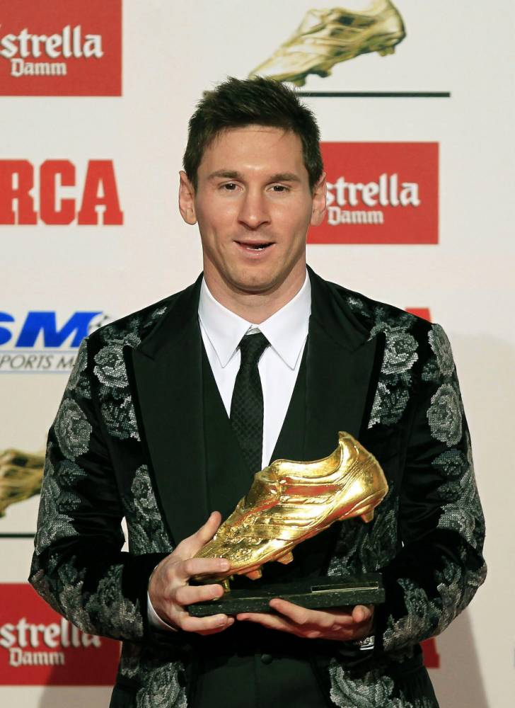 epa03958214 FC Barcelona's Argentinian striker Lionel Messi poses for photographers with the Golden Boot trophy during a ceremony in Barcelona, north-eastern Spain, 20 November 2013. Messi received the award as top scorer in all European leagues of the 2012-2013 season with a total of 50 goals. Messi also won the Golden Boot award in the 2009-10 and 2011-12 season.  EPA/ANDREU DALMAU