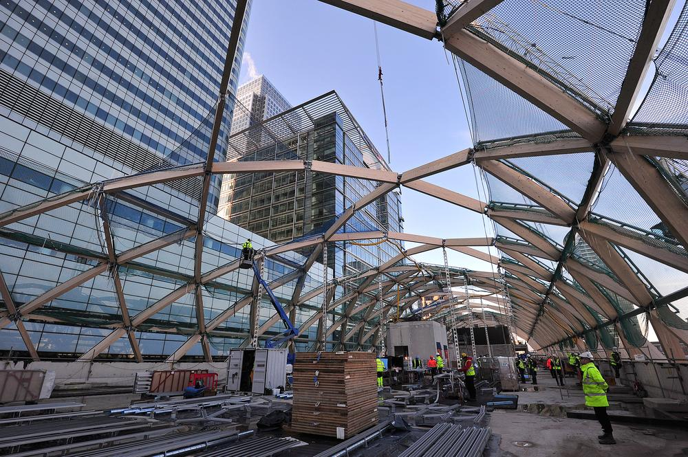 Builders work on a timber lattice roof above the Canary Wharf Crossrail station and retail development site in east London, on November 26, 2013. The Crossrail project, which is expected to be completed in 2018, will link Berkshire, west of London with Essex, east of London, at a cost of approximately GBP14.8bn (17.6bn euros/23.9bn USD) AFP PHOTO / CARL COURT CARL COURT/AFP/Getty Images