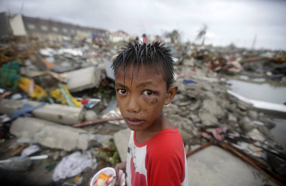 epa03977282 (01/14) A file picture dated 10 November 2013 shows 11-year-old supertyphoon survivor Joshua Cator scavenging for food and reusable material in destroyed houses in the devastated city of Tacloban, Leyte province, Philippines.  EPA/DENNIS M. SABANGAN PLEASE REFER TO ADVISORY NOTICE  (epa03977281) FOR FULL FEATURE TEXT