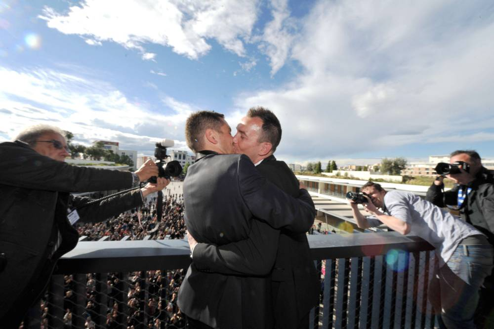 (FILES)-- A file picture taken on May 29, 2013,  in the city hall in Montpellier, shows Vincent Autin (R) and Bruno Boileau kissing on a balcony in front of the crowd after their marriage, France's first official gay marriage. France is the 14th country to legalise same-sex marriage, an issue that has also divided opinion in many other nations. The definitive vote in the French parliament came on April 23 when the law was passed legalising both homosexual marriages and adoptions by gay couples.   AFP PHOTO POOL / GERARD JULIENGERARD JULIEN/AFP/Getty Images