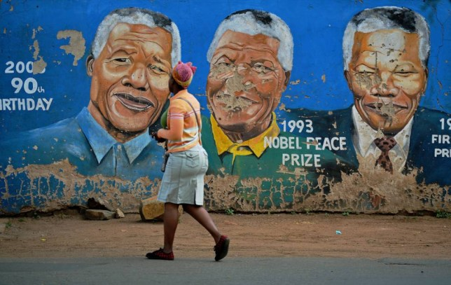 A woman walks past murals of the late Nelson Mandela in Soweto two days after his death. (Picture: Getty)