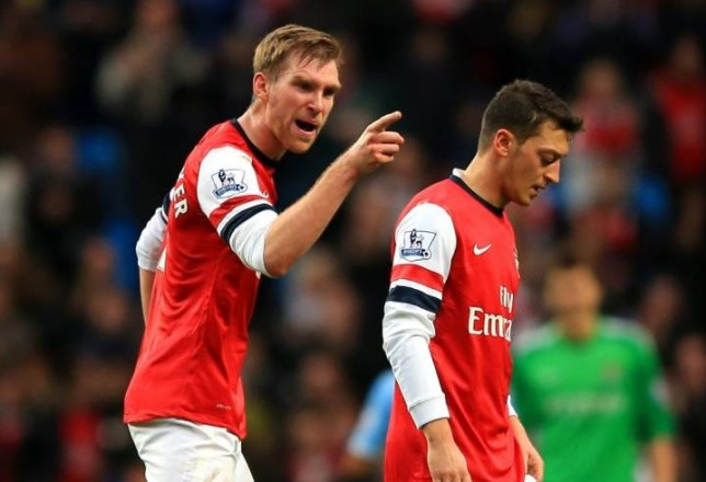 MANCHESTER, ENGLAND - DECEMBER 14:  Per Mertesacker of Arsenal has words with Mesut Oezil of Arsenal during the Barclays Premier League match between Manchester City and Arsenal at Etihad Stadium on December 14, 2013 in Manchester, England.  (Photo by Richard Heathcote/Getty Images)
