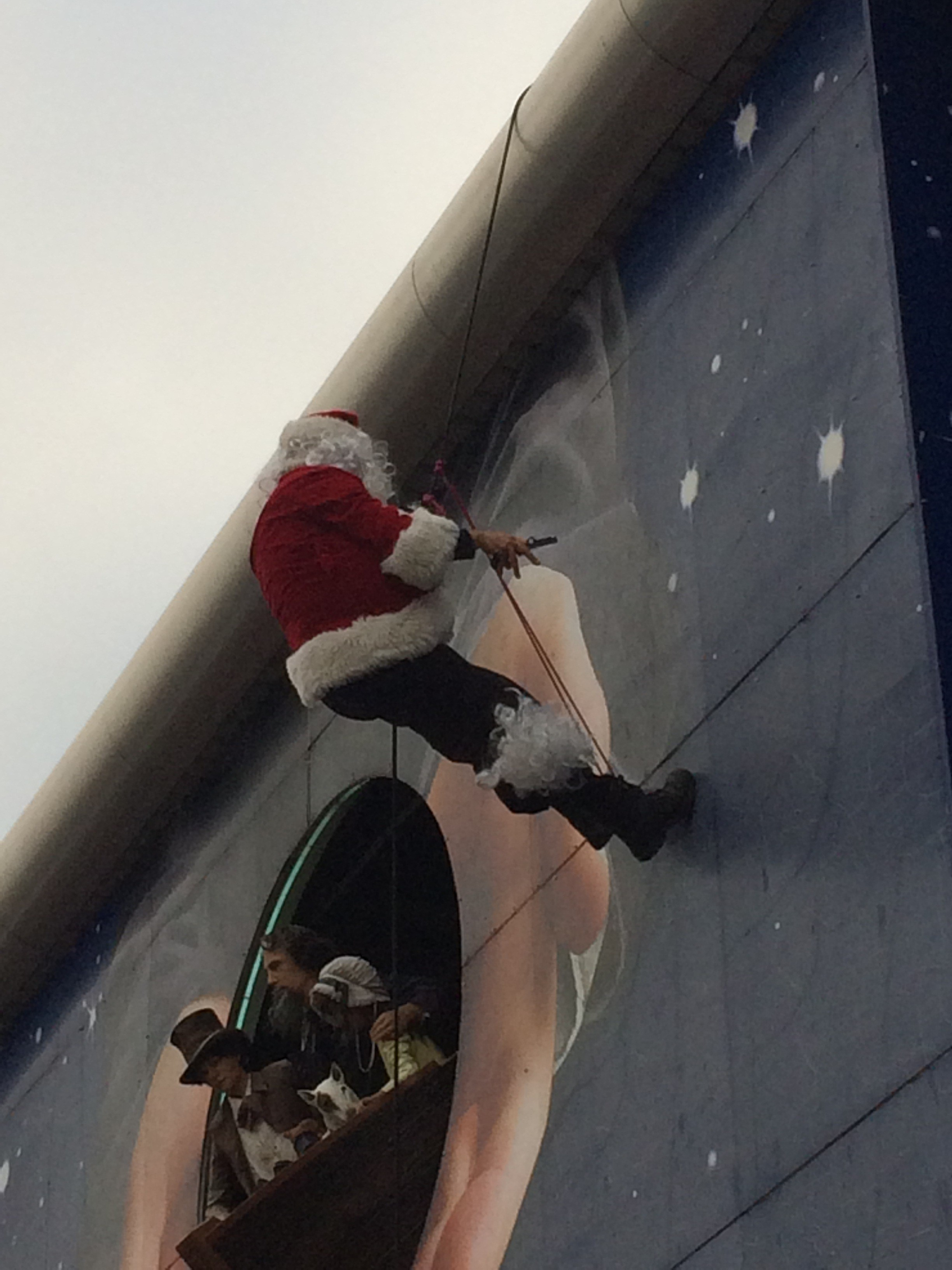 Abseiling Santa has to cut his beard to free himself in front of amused shoppers