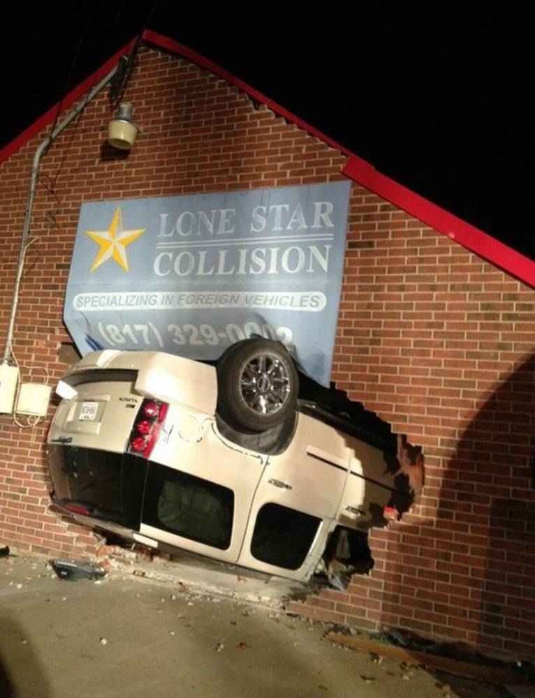 Car crashes upside down into side of a collision repair shop