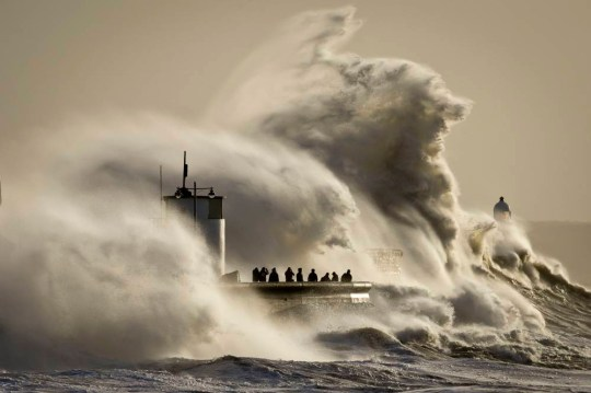 People watch and photograph enormous waves as they break on Porthcawl harbour, South Wales, where very strong winds and high seas create dangerous weather conditions. PRESS ASSOCIATION Photo. Picture date: Monday January 06, 2014. See PA story WEATHER Flood. Photo credit should read: Ben Birchall/PA Wire