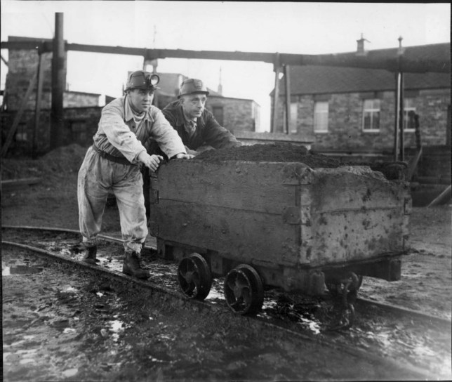 Coalmine trainees working at the pit Pic shows Footballer Bobby Collins of Glasgow Celtic FC who is taking a course to become a miner, seen pushing a load with his instructor Thomas McPhillip at the Muireockhall training centre . REXSCANPIX.