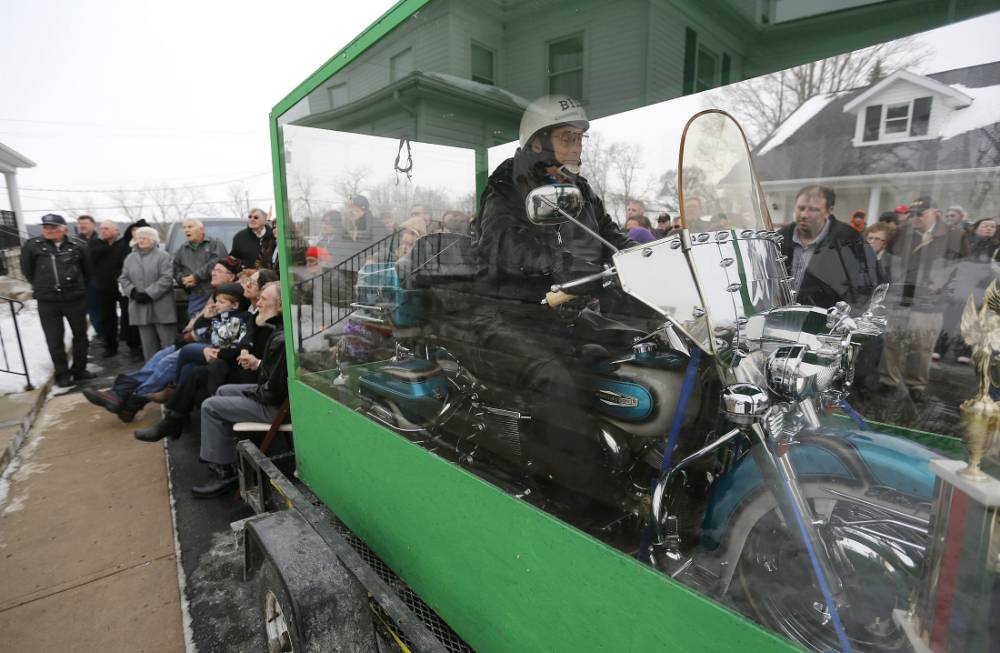 The body of Bill Standley secured to his 1967 Harley Davidson rests inside a plexiglass box during his funeral service in Mechanicsburg, Ohio on Friday, Jan. 31, 2014.  Standley's family said he'd been talking about it for years and liked to take people to the garage to show off the unusual casket his two sons had built for him. He told people he didn't just want to ride off to heaven, he wanted the world to see him do it in the big see-through box. (AP Photo/Columbus Dispatch, Jonathan Quilter)