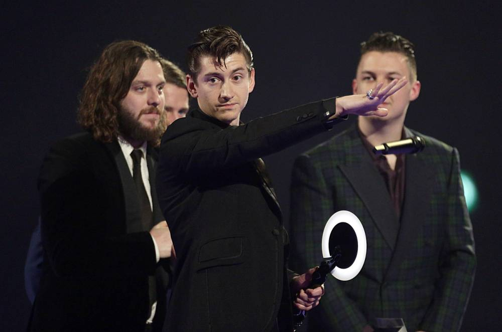 Alex Turner of the Arctic Monkeys on stage after winning Best British Group at the 2014 Brit Awards