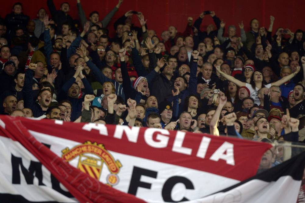 Manchester United fans cheer before the round of 16 Champions League football match Olympiakos vs Manchester United at Karaiskaki Stadium in Athens on February 25, 2014. AFP PHOTO / ARIS MESSINISARIS MESSINIS/AFP/Getty Images