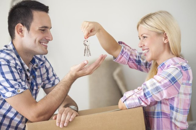 Moving into new home young happy couple, girl holding house keys and giving her boyfriend LuckyBusiness/LuckyBusiness