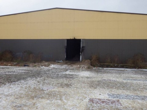 Criminals cut a 'lorry-sized' hole in the side of warehouse, dump mountains of waste inside