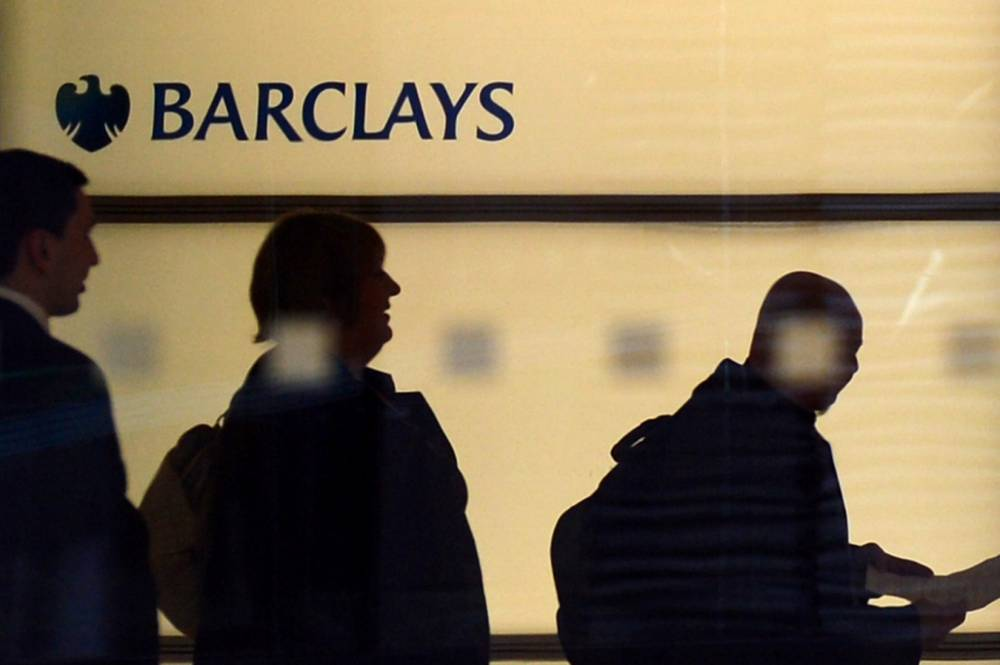 People walk past a Barclays logo at the bank's headquarters in Canary Wharf in east London