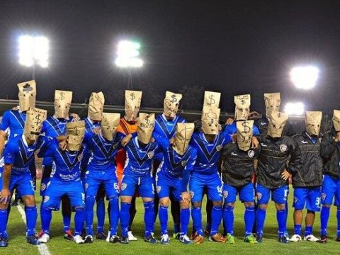 Angry footballers protest at unpaid wages by wearing brown paper bags over their heads for official photograph