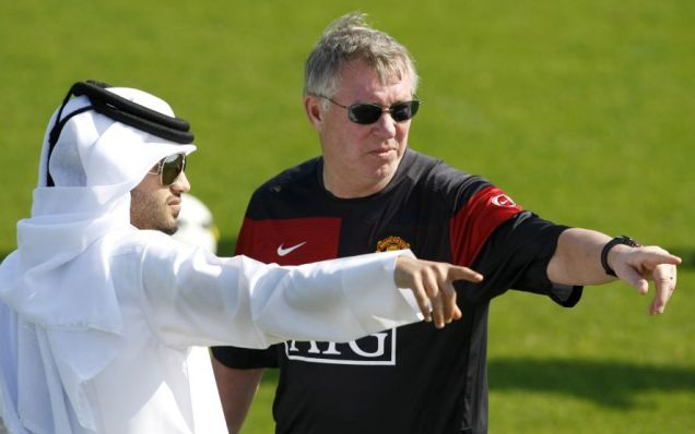 Manchester United's head coach Sir Alex Ferguson gestures next to a Qatari official as he directs his team during a training session in Doha