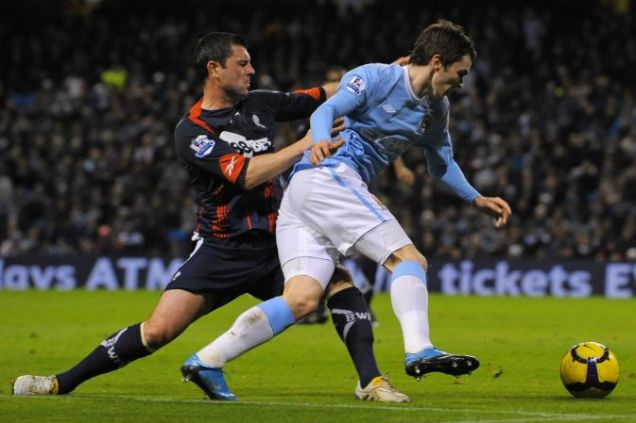 Bolton Wanderers' Paul Robinson (L) concedes a penalty with a challenge on Manchester City's Adam Johnson