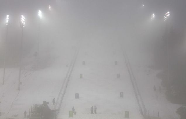 Course workers prepare the freestyle skiing moguls competition site as rain falls on Cypress Mountain and creates fog