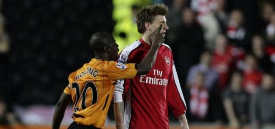 Arsenal's Nicklas Bendtner is poked in the eye by Hull's George Boateng