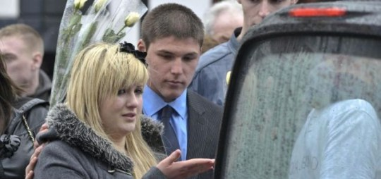 Kiss: Andrew Holkham and a friend watch the hearse carrying his brother, Daniel