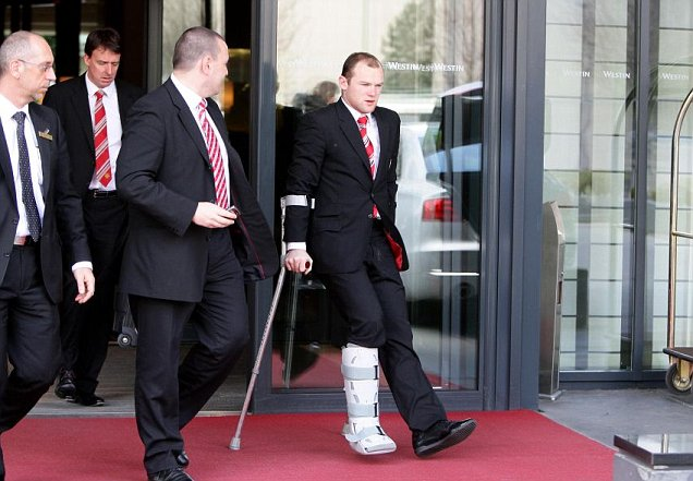 Manchester United's Wayne Rooney leaves the Westin Grand Hotel in Munich on crutches