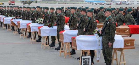 Soldiers stand in attention next to the coffins of 30 victims who perished in Saturday's aeroplane crash