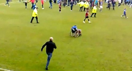 The disabled supporter's carer rushes out to catch the runaway wheelchair
