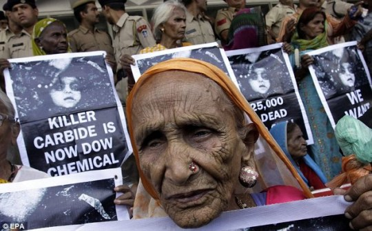 Elderly Bhopal gas tragedy survivors hold posters as they wait for the verdict at the local court in Bhopal,
