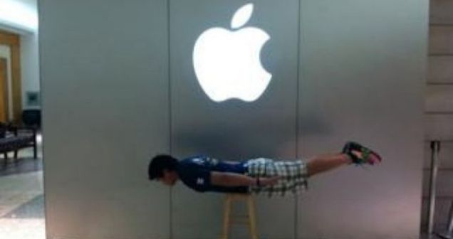 One Apple Store employee planks himself on a stool beneath the firm's logo
