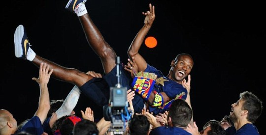 Barcelona's players lift Eric Abidal into teh air to celebrate their league triumph