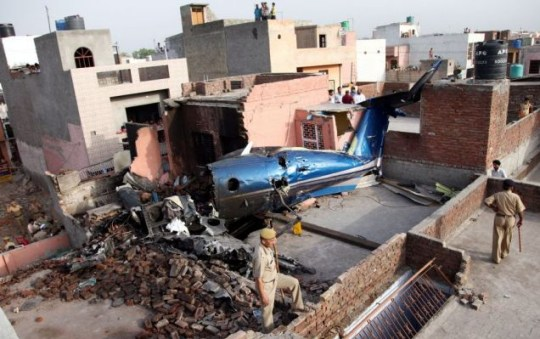 Smouldering: The charred remains of an aircraft that crashed into a house near New Delhi Picture: EPA
