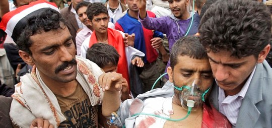 Wounded: An injured man is taken to hospital after clashing with security forces in Yemen (Pic: AP)