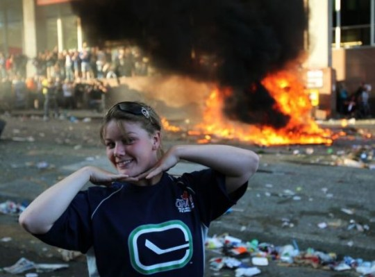 A Vancouver Canucks fan poses for photos in front of an overturned pickup truck as it burns