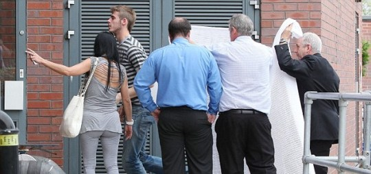 Manchester United staff try in vain to shield new signing David De Gea from prying eyes as he goes for a medical (Eamonn and James Clarke)