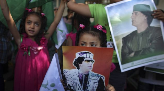 Gaddafi's supporters protest against coalition airstrikes on a government-organised tour