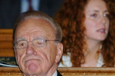 News Corporation chairman Rupert Murdoch sitting in front of Rebekah Brooks