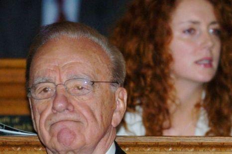 News Corporation chairman Rupert Murdoch sitting in front of Rebekah Brooks