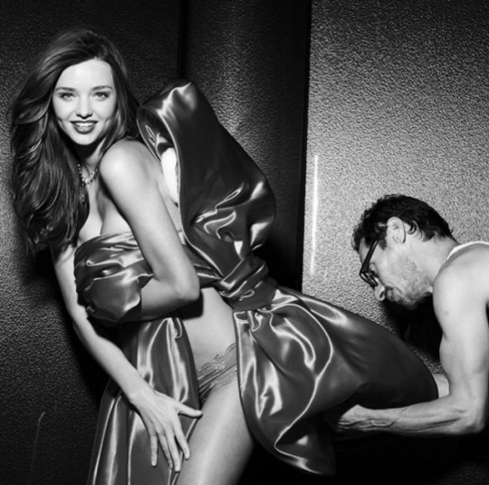 Miranda Kerr, smiles posing, while photographer Russell James makes sure everything is perfect