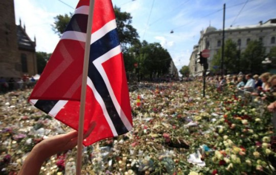 Grieving: A woman touches a Norwegian flag as people continue to gather outside Oslo Cathedral (Picture: AP)