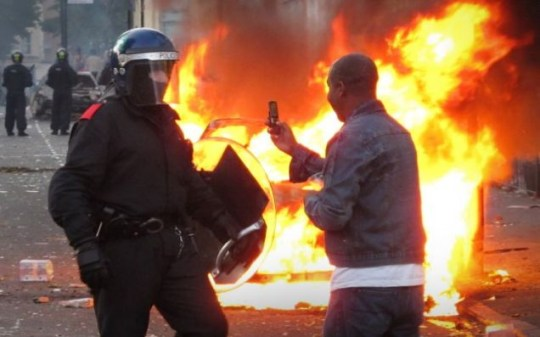 'Hang on, just let me TwitPic this' - a Hackney resident takes pictures of a police officer during the riots on August 8 (Picture: Getty)