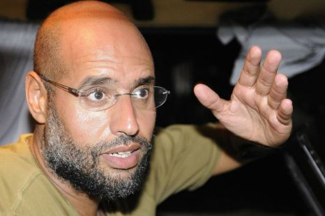 Saif Al-Islam, son of Libyan leader Muammar Gaddafi, gestures as he talks to reporters in Tripoli last today