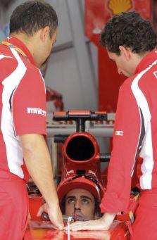 Fernando Alonso chats with his Ferrari mechanics (Picture: AP)