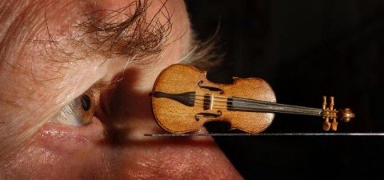 The eye of former Royal Philharmonic Orchestra Cellist David Edwards is pictured his dolls house violin.